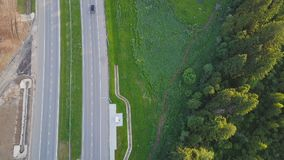 Aerial view at the country highway passing near forest in evergreen northern forests. Clip. Top view of the motorway. Near the forest stock photos