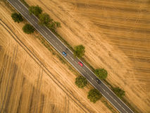 Aerial view of a country road amid fields. With a car on it Royalty Free Stock Images