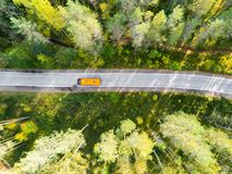Aerial view of a country road in the forest with moving cars. Beautiful landscape. Captured from above with a drone. Aerial bird`. S eye road with car. Aerial stock images