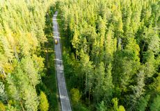Aerial view of a country road in the forest with moving cars. Beautiful landscape. Captured from above with a drone. Aerial bird`. S eye road with car. Aerial royalty free stock image