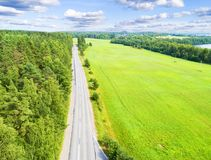 Aerial view of a country road in the forest with moving cars. Landscape. Captured from above with a drone. Aerial bird`s eye road royalty free stock photography