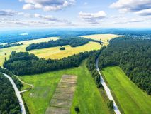 Aerial view of a country road in the forest with moving cars. Landscape. Captured from above with a drone. Aerial bird`s eye road. With car. Aerial top view stock photos