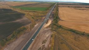 Aerial view of a country road next to the countryside. Aerial view on tracks between agriculture fields stock video footage
