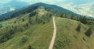 Aerial view of country road over hill in mountain stock footage