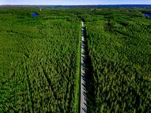 Aerial view of a country road with red car in the middle of green summer forest royalty free stock photos