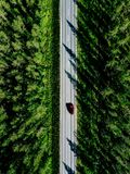 Aerial view of a country road with red car in the middle of green summer forest stock photo
