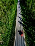 Aerial view of a country road with red car in the middle of green summer forest royalty free stock image