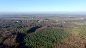 Aerial view of countryside landscape with forests and farmlands during morning blue day stock video