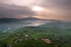 Aerial view on countryside and mount Etna. Aerial view of countryside in dawn mist on the lake and on the background mount Etna. The picture was taken from Agira Stock Photos