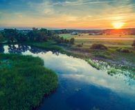 Aerial view of countryside and river in evening. Sunset over the river stock photos