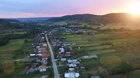 Aerial view of countryside village and crops at sunset stock video footage