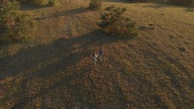 Couple runing at sunset. Aerial view of couple runing at sunset stock footage