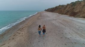 Aerial view of couple running on beach.  stock footage