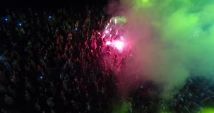 Aerial view of crowd with red signal flare dancing on music festival