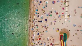 Aerial view of a crowded beach in a sunny hot day. Yellow sand and umbrellas. Aerial view of the beach filled with people on a hot sunny day. Sun umbrellas stock footage