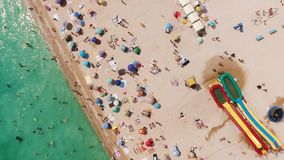 Aerial view of a crowded beach in a sunny hot day. Yellow sand and umbrellas. Aerial view of the beach filled with people on a hot sunny day. Sun umbrellas stock video