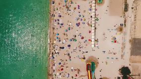 Aerial view of a crowded beach in a sunny hot day. Yellow sand and umbrellas. Aerial view of the beach filled with people on a hot sunny day. Sun umbrellas stock video footage
