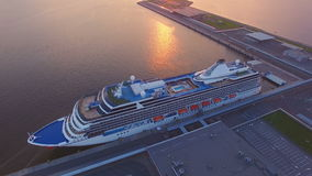 Aerial view of the Cruise Ship in Harbor at Sunset. Aerial view of the Beautiful cruise liner is in port of St. Petersburg at sunset. He is white, with a stock video footage
