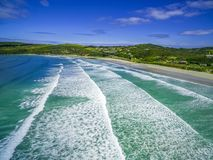 Aerial view of crushing ocean waves and white sandy beach. Stock Photos