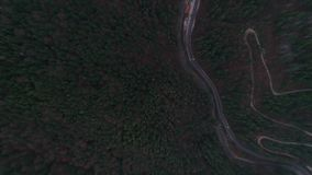 Aerial view of a curved winding road betwen big mountains 4k 60fps. Aerial view of a curved winding road betwen big mountains stock footage