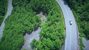 Aerial view of a curved winding road with cars passing. Mountain road. Hairpin turn in the forest. Aerial view of a curved winding mountain road with cars stock video