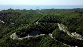 Aerial view of a curved winding road trough the mountains to Sochi, Russia stock video footage