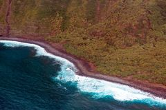 Pacific surf pounds the Molokai coast in Hawaii. Aerial view of the curvy coastline, green shore, and pounding surf on the island of Molokai, Hawaii Stock Photo
