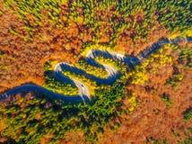 Aerial view of curvy road through autumn colored forest. Stunning aerial view of winding road through autumn colored forest Royalty Free Stock Photos