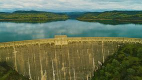 Aerial view of dam on a country side green grass live stock mountains and lakes power company. Mountains and lakes day time sun set stock footage