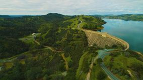 Aerial view of dam on a country side green grass live stock mountains and lakes power company. Mountains and lakes day time sun set stock video