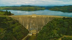 Aerial view of dam on a country side green grass live stock mountains and lakes power company. Mountains and lakes day time sun set stock video footage