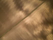 Aerial view of a dappled brown meadow and dirth road Royalty Free Stock Images