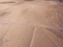 Aerial view of a desert landscape on the island of Lanzarote, Canary Islands, Spain. A man with a orange shirt walking in a dese. Aerial view of a desert stock photography