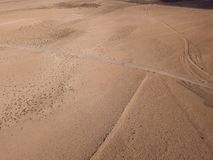 Aerial view of a desert landscape on the island of Lanzarote, Canary Islands, Spain. A man with a orange shirt walking in a dese. Aerial view of a desert royalty free stock photography