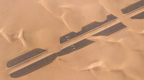 Aerial view of a desert road being run over by sand dunes. royalty free stock photo