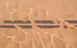 Aerial view of a desert road being run over by sand dunes. stock photography