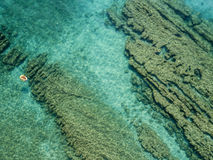 Aerial view of a dinghy in the water floating on a transparent sea. Bathers at sea. Zambrone, Calabria, Italy. Diving relaxation and summer vacations. Italian royalty free stock photography