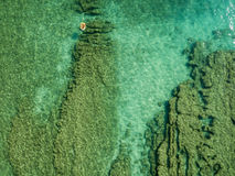 Aerial view of a dinghy in the water floating on a transparent sea. Bathers at sea. Zambrone, Calabria, Italy. Diving relaxation and summer vacations. Italian royalty free stock photo