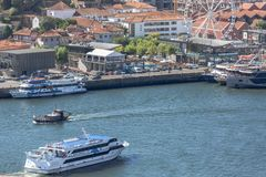 Aerial view at the Douro river, with cruisers and recreative boats, Gaia downtown buildings and ferris wheel as background. Oporto/Portugal - 10/02/2018 : Aerial stock photography