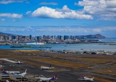 Aerial view of downtown Honolulu and HNL airport in Hawaii. Honolulu, Hawaii, USA - May 25, 2015: Aerial view of downtown Honolulu, Diamond Head and airplanes on Royalty Free Stock Images