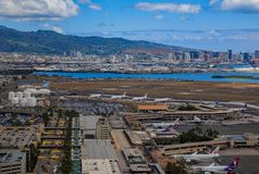 Aerial view of downtown Honolulu and HNL airport in Hawaii. Honolulu, Hawaii, USA - May 25, 2015: Aerial view of downtown Honolulu and airplanes parked on the Royalty Free Stock Photos