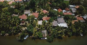 Aerial view drone descending over lovely tropical coast resort hotels on a jungle river bank with lush green palm trees.
