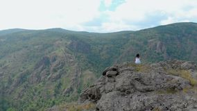 Aerial view, drone fly over the seated girl on a cliff face. Drone shot, aerial view, camera fly forward over the seated girl on a cliff face stock footage