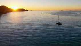 Aerial view with drone flying low over the ocean water. Between parked sailing boats in a bay with nice sunset vibrant colors in the horizon stock video footage