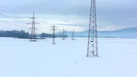 Aerial view with drone flying between wires of big electrical towers. On a cloudy winter field landscape covered with white cold snow stock video