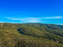 Aerial view of drone, forest in mountain with wind turbines on ridge. In Portugal blue environment electricity mill technology environmental nature windmill royalty free stock photography
