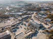 Aerial view from drone of industrial area with warehouses, buildings, trucks, industry equipment, heavy transport. Production of building materials from above stock photography