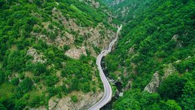 Aerial view of drone over mountain road and curves going through forest landscape.  stock video footage