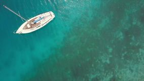 Aerial view from drone: sailing boat and then pure blue waters with sunbeams