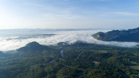 Aerial view drone shot of flowing fog waves on mountain tropical rainforest stock photos
